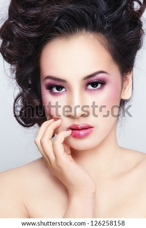Close-up portrait of young beautiful asian girl with curly hair and stylish make-up - stock photo