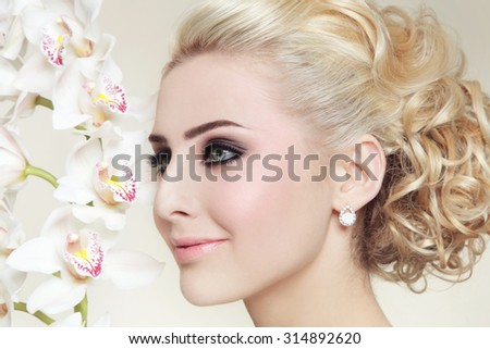 Close-up portrait of young beautiful blond girl with smoky eyes and stylish prom hairdo - stock photo