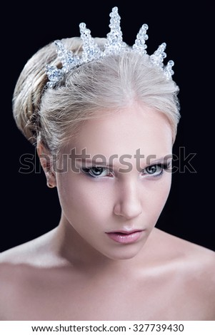 Close-up portrait of young beautiful blond woman, wearing in jewelry crown with crystals, looking at camera, isolated on black background - stock photo