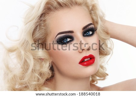 Close-up portrait of young beautiful blond woman with smoky eyes and red lips - stock photo