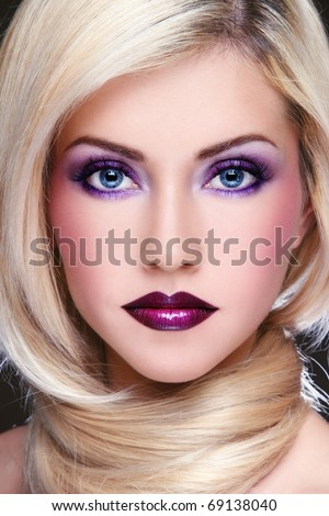 Close-up portrait of young beautiful blond woman with stylish violet make-up