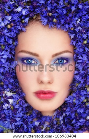 Close-up portrait of young beautiful blue-eyed woman with bluettes around her face - stock photo