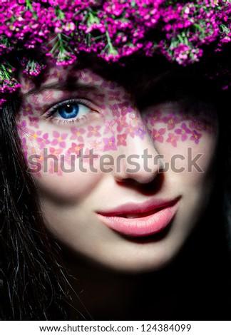 Close-up portrait of young beautiful blue-eyed woman with flowered wreath and creative make up