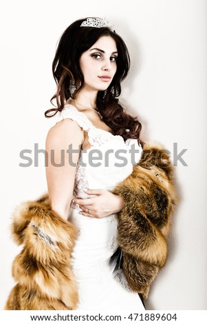 close-up portrait of young beautiful bride in a wedding dress with a wedding makeup and hairstyle. young bride in a fur coat from a red fur