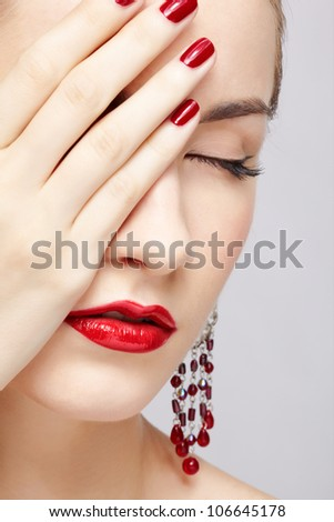 close-up portrait of young beautiful brunette woman in ear-rings closing half of her face with manicured hand - stock photo