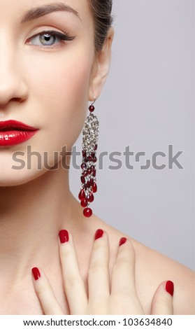 close-up portrait of young beautiful brunette woman in ear-rings touching her shoulder with manicured fingers - stock photo
