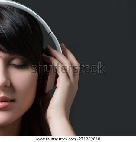 Close-up portrait of young beautiful brunette woman listening to music and holding white headphones - stock photo