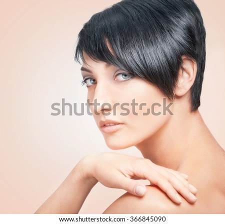 Close-up portrait of young beautiful brunette woman on light pink background - stock photo