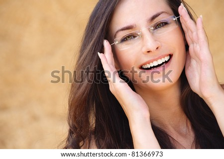Close-up portrait of young beautiful brunette woman wearing glasses against beige background. - stock photo