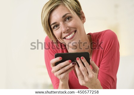 close up portrait of young beautiful Caucasian woman with shorts and modern hair style happy on couch using internet texting on mobile phone app relaxed and cheerful at home living room - stock photo