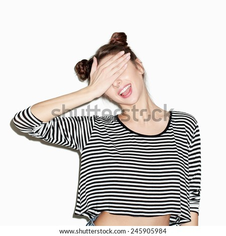 Close up portrait of young beautiful girl having fun and hiding her face with hand. Natural makeup and top knot hairdo. White background, not isolated. Inside. - stock photo