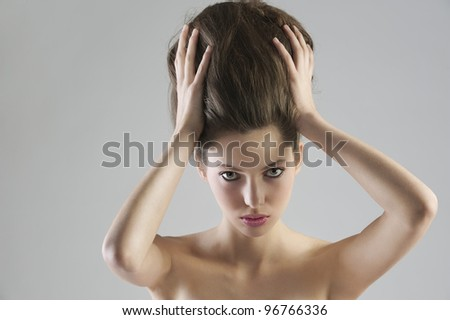 close up portrait of young beautiful girl holding her updo hair posing on grey background