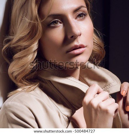 Close-up portrait of young beautiful girl with curly blond hair and natural make up in light coat on dark background. Worried, anxious, sad, depressed emotions. Looking up side of camera