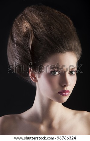 close up portrait of young beautiful girl with dark hair and creative hairstyle posing over black background - stock photo