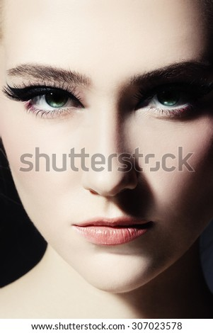 Close-up portrait of young beautiful girl with fancy cat eye make-up - stock photo