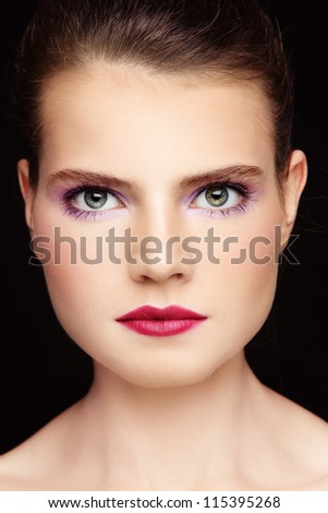 Close-up portrait of young beautiful green-eyed woman with fancy make-up