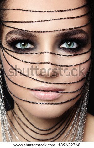 Close-up portrait of young beautiful green-eyed woman with fancy make-up and chains over her face - stock photo