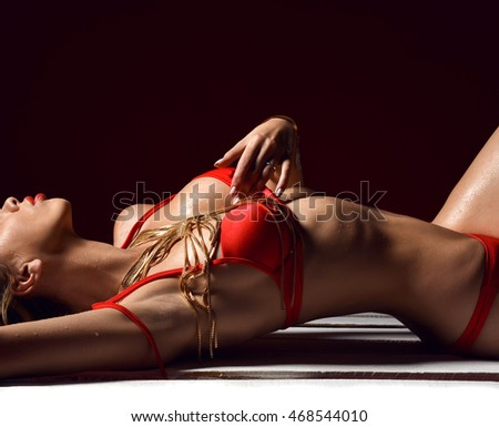 CLose up portrait of young beautiful sexy woman posing lying in summer fashion body red bikini swimwear on wooden pallet on a dark background