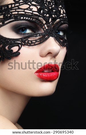 Close-up portrait of young beautiful stylish woman in black lacy mask - stock photo