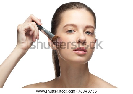 Close-up portrait of young beautiful woman applying makeup, isolated on white background