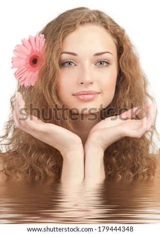 Close-up portrait of young beautiful woman in water holding her hands near the face. Beauty treatment concept  - stock photo