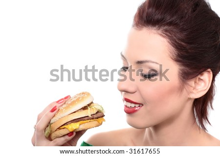 close-up portrait of young beautiful woman is eating big mac isolated on white
