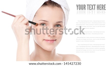 Close-up portrait of young beautiful woman with brush for make-up. Eye zone