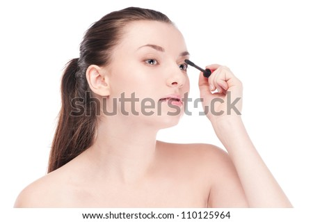 Close-up portrait of young beautiful woman with brush for make-up. Mascara, eye zone - stock photo