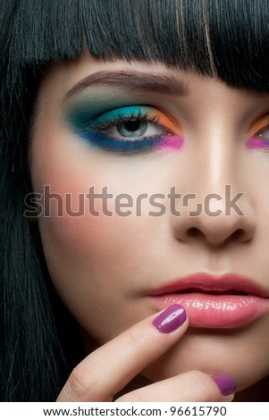 Close-up portrait of young beautiful woman with colorful stylish make-up and manicure - stock photo