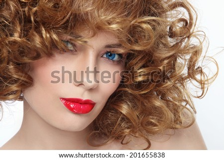 Close-up portrait of young beautiful woman with curly hair and red lipstick, selective focus - stock photo