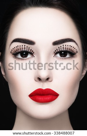 Close-up portrait of young beautiful woman with fancy false eyelashes and matte red lipstick