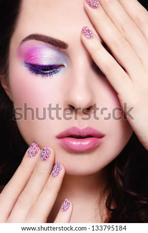 Close-up portrait of young beautiful woman with fancy make-up and caviar manicure