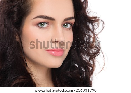 Close-up portrait of young beautiful woman with fresh clean make-up and curly hair over white background - stock photo