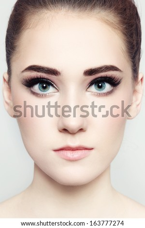 Close-up portrait of young beautiful woman with fresh make-up - stock photo
