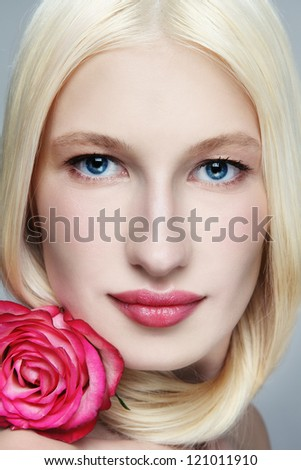 Close-up portrait of young beautiful woman with long blond hair and clear make-up - stock photo