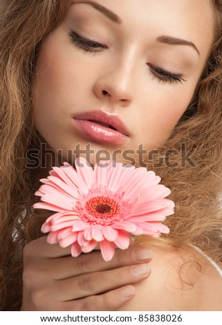 Close-up portrait of young beautiful woman with long curly hair holding pink flower - stock photo