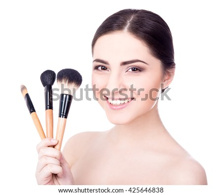 close up portrait of young beautiful woman with make up brushes isolated on white background - stock photo