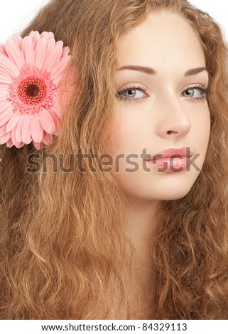 Close-up portrait of young beautiful woman with pink flower in her hair. Isolated on white background - stock photo
