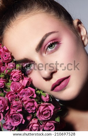 Close-up portrait of young beautiful woman with pink roses - stock photo