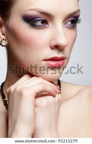 close-up portrait of young beautiful woman with purple eye shadow on gray - stock photo