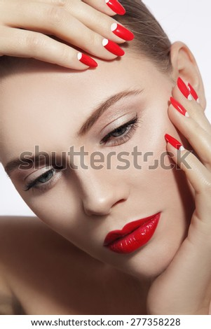 Close-up portrait of young beautiful woman with red lips and fancy manicure over white background - stock photo