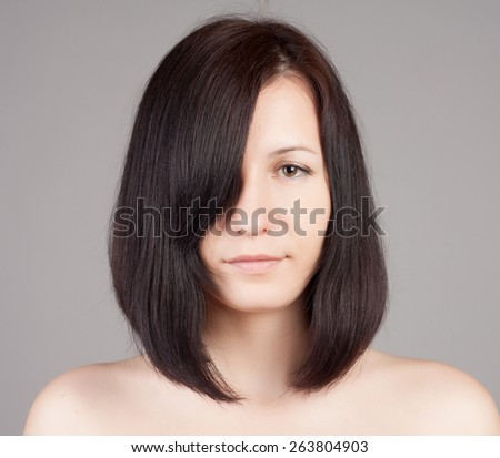 Close-up portrait of young beautiful woman with short hairstyle. Beautiful haircut. Short straight healthy hair.