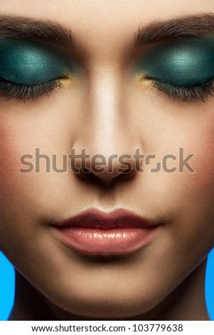 Close-up portrait of young beautiful woman with stylish bright make-up with closed eyes - stock photo