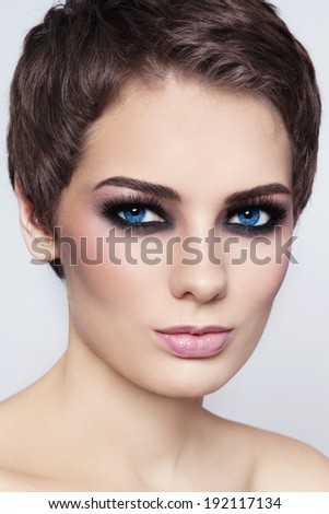 Close-up portrait of young beautiful woman with stylish short haircut and smokey eyes - stock photo