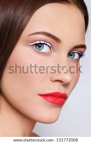 Close-up portrait of young beautiful woman with stylish white eyeliner and coral matte lipstick - stock photo