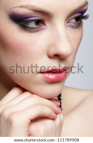 close-up portrait of young beautiful woman with violet eye shadow on gray - stock photo