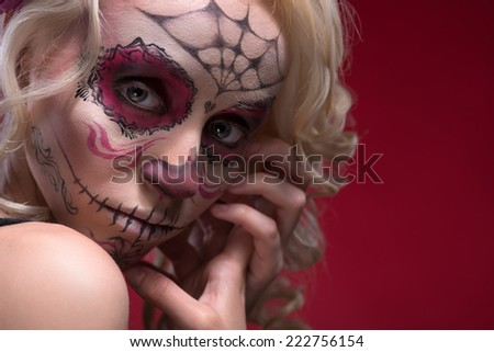 Close-up portrait of young blond girl with sad face with Calaveras makeup upset looking at the camera while holding her hands near face isolated on red background with copy place - stock photo