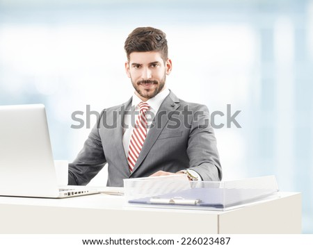 Close-up portrait of young broker analyzing data on laptop while sitting at stock exchange. Looking a Camera