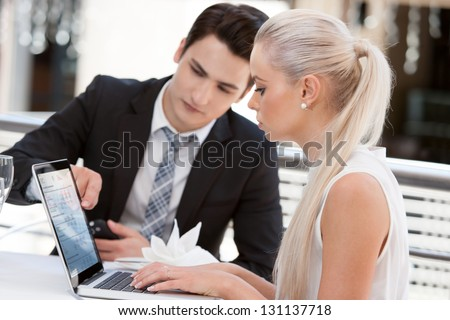 Close up portrait of young business partners reviewing work at lunch. - stock photo