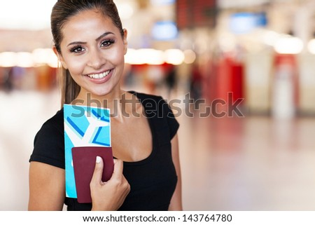 close up portrait of young businesswoman at airport holding flight ticket - stock photo